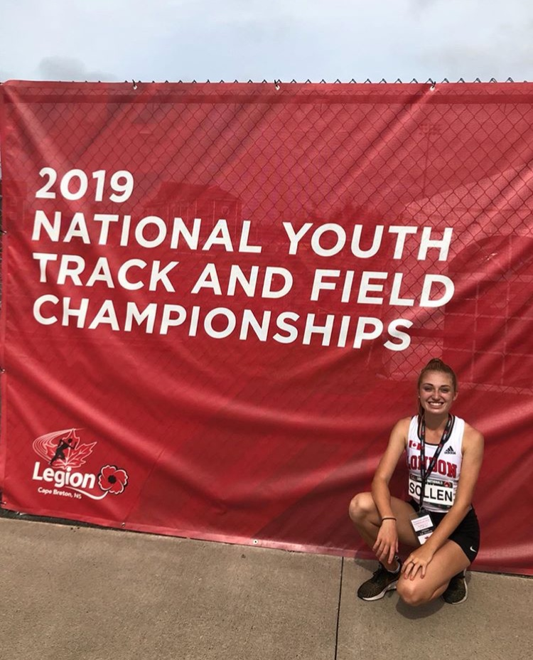 Female athlete poses in front of the Legion Nationals 2019 sign on the track.
