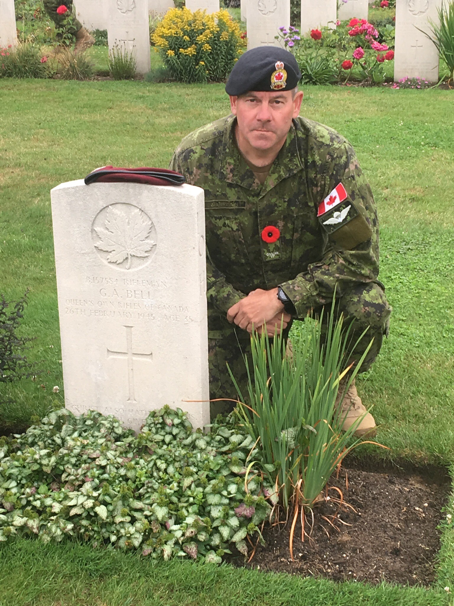 Lee Harrison poses at George Armstron Bell's grave stone. Lee's QOR Beret is on top of the stone for the photo so he has his head dress too.