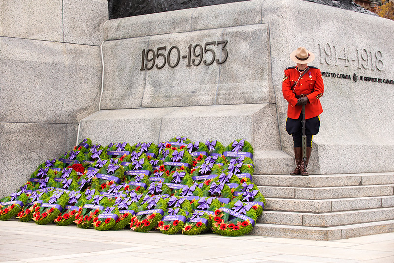 RCMP officer stands guard at the National War Memorial on Remembrance Day. To his left are commemorative wreaths left by attendees.