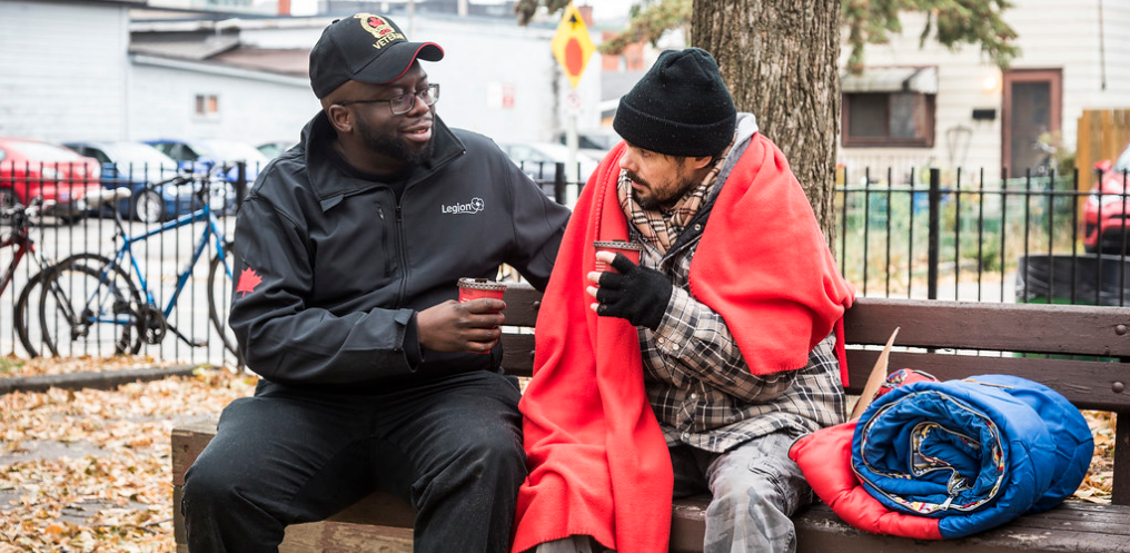 Legionnaire sits with a homeless Veteran on a park bench. They are drinking coffee and chatting.