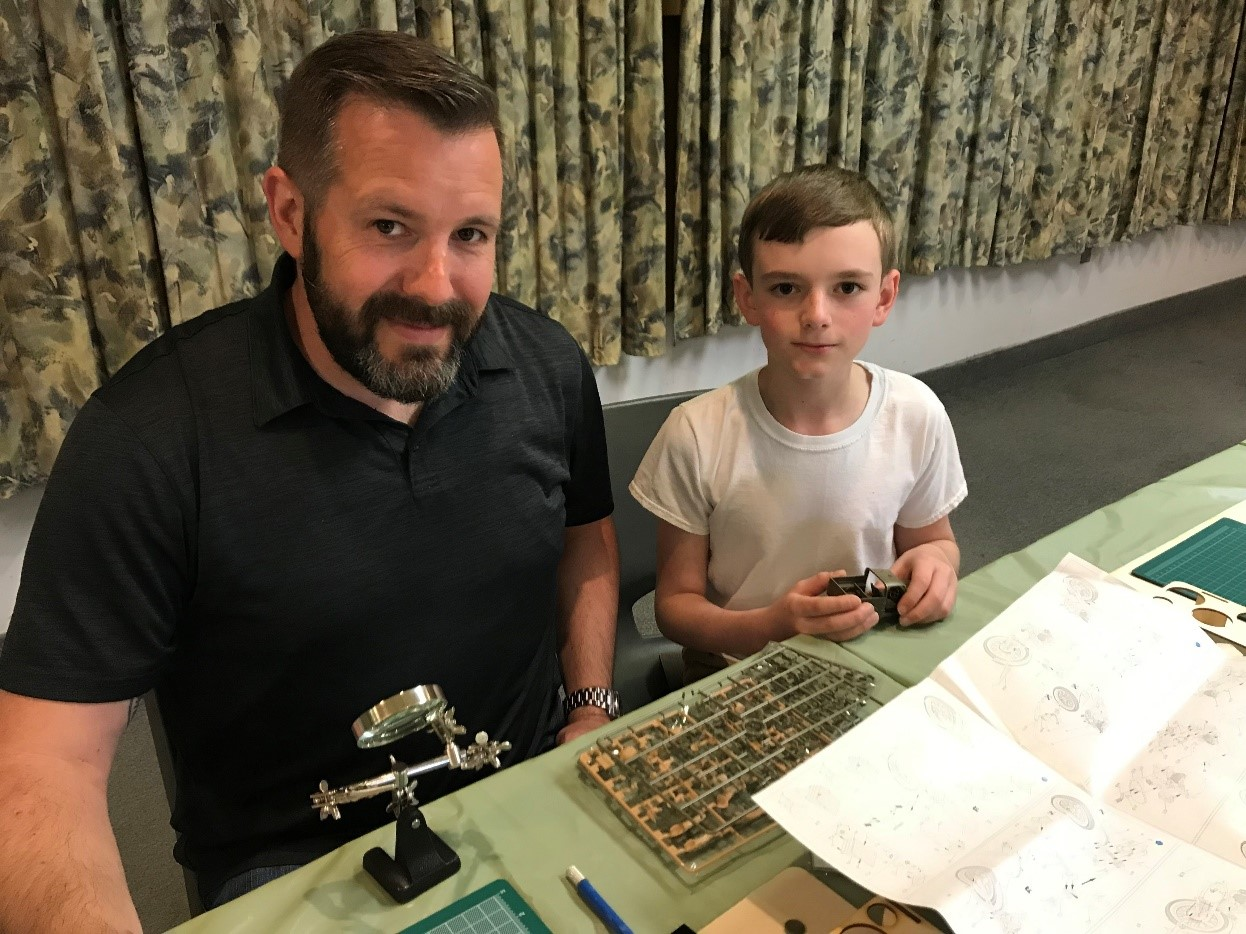 Father and young son enjoy model building together at an Operation VetBuild event.