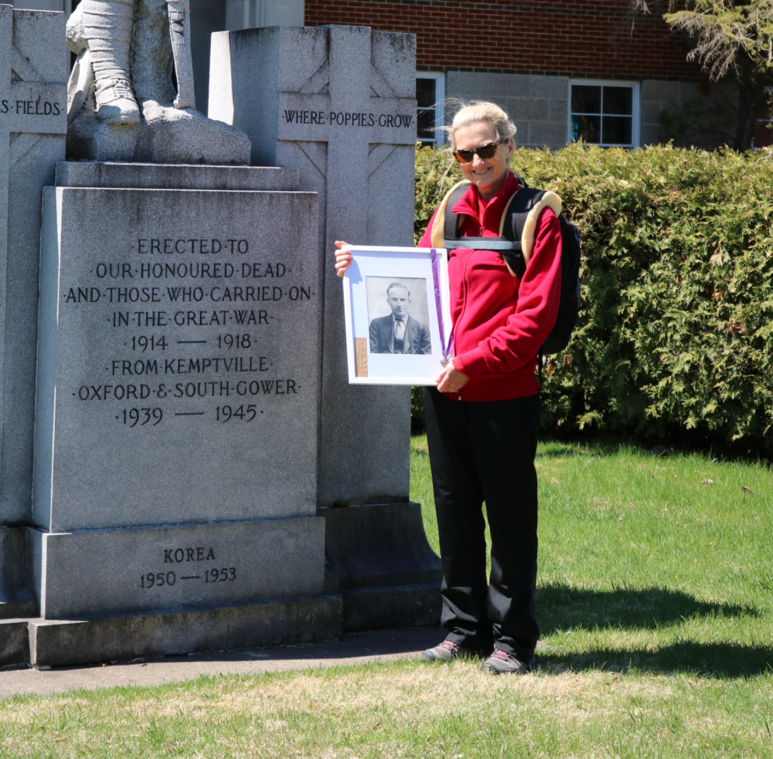 Joan Cook stands at the Kemptville Cenotaph holding a photograph of her grandfather.